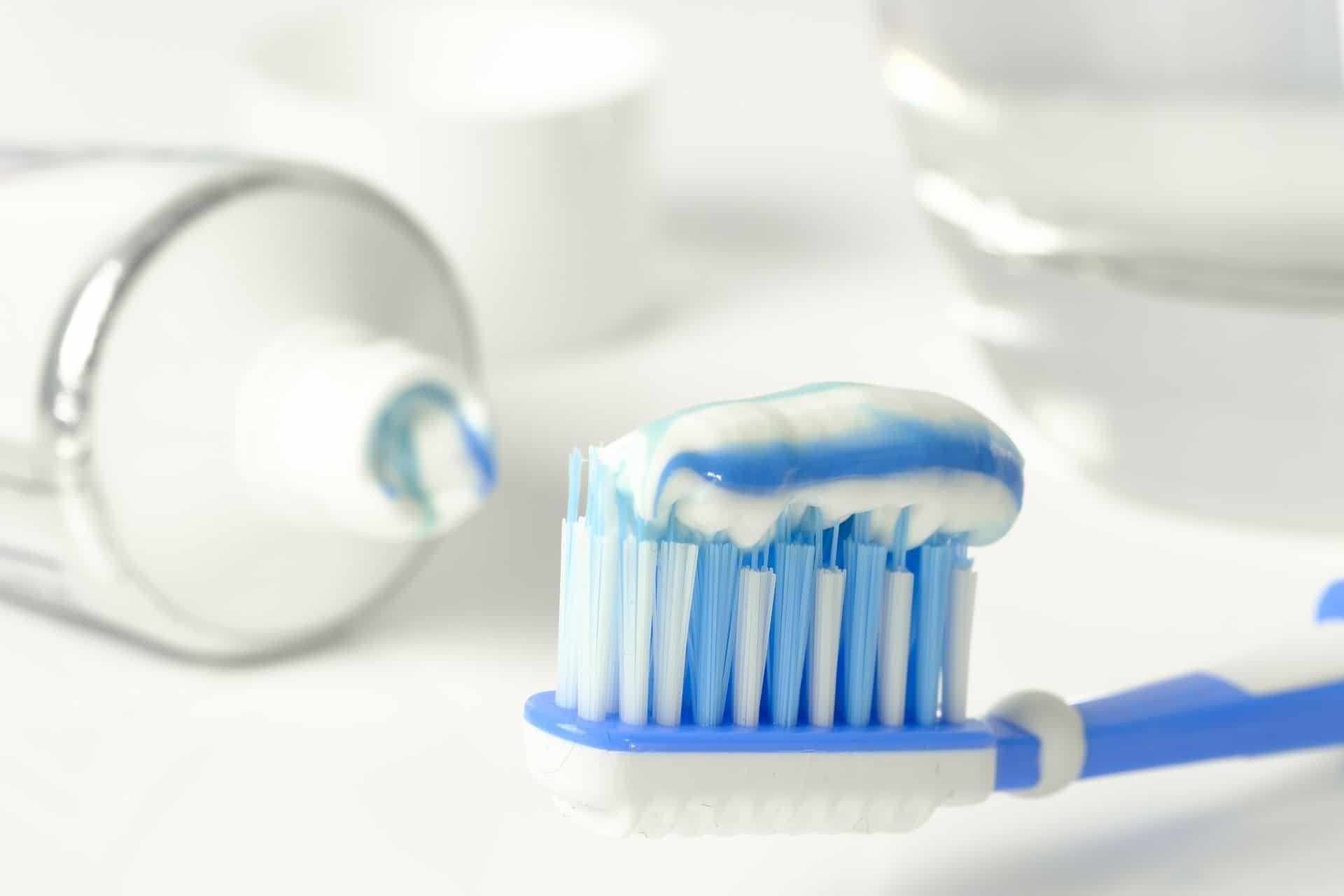 Imagem de escova de dentes branca e azul com pasta de dente branca e azul com tubo de pasta de dentes ao fundo sobre uma bancada branca.