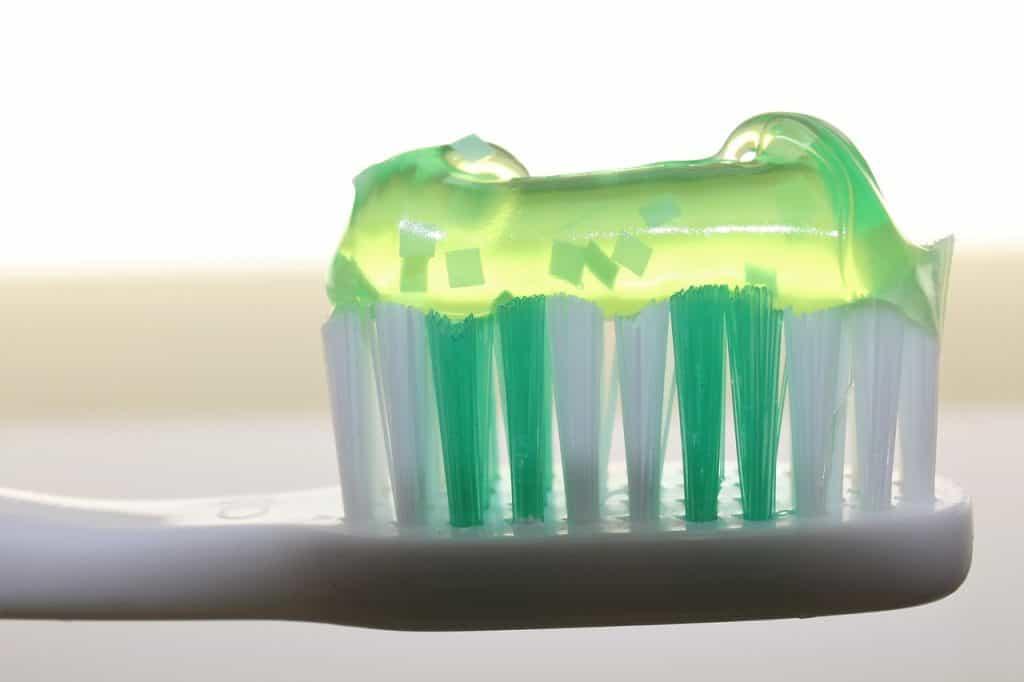Imagem de uma escova de dente com cerdas brancas e verdes e pasta de dente verde.