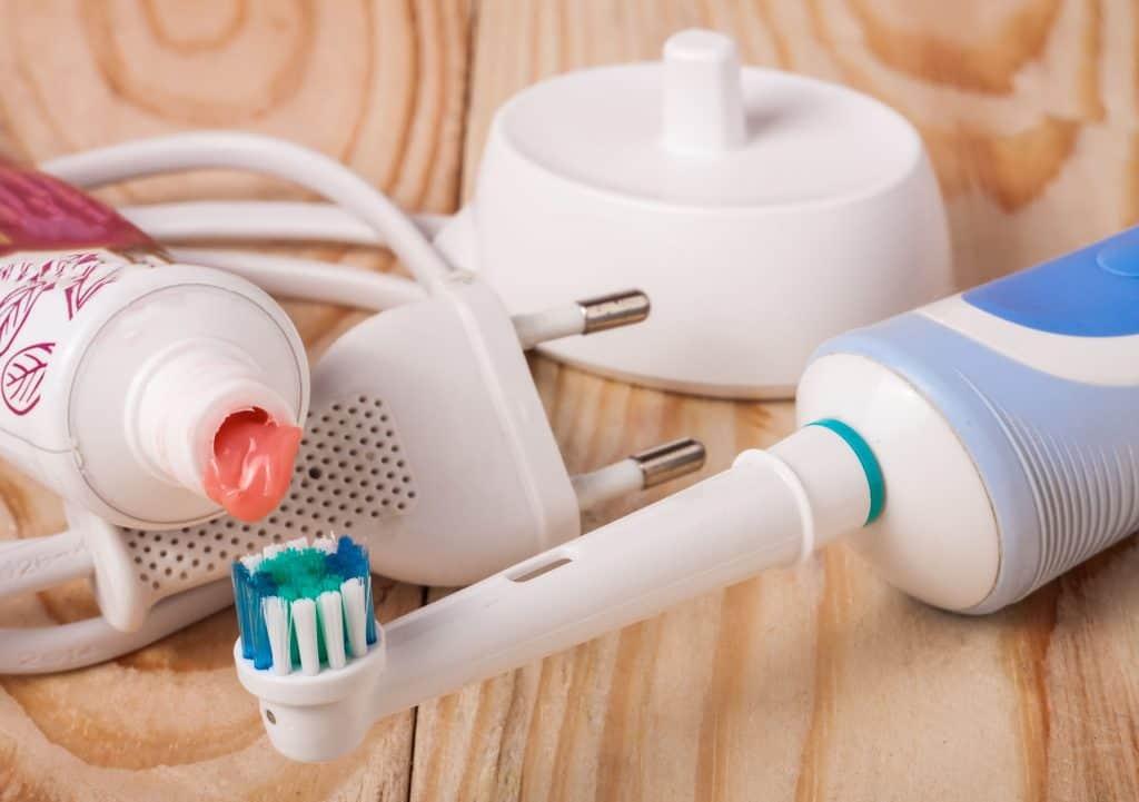 Imagem de escova elétrica e pasta de dentes.