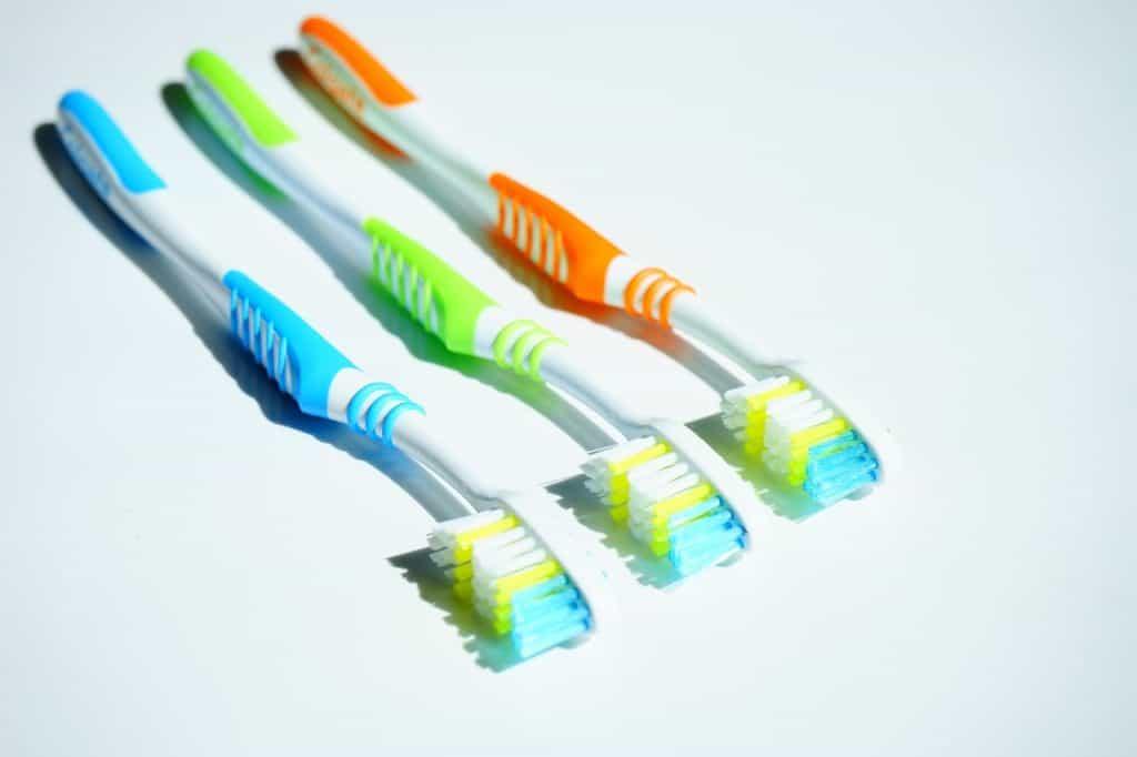 Imagem de três escovas de dentes lado a lado.