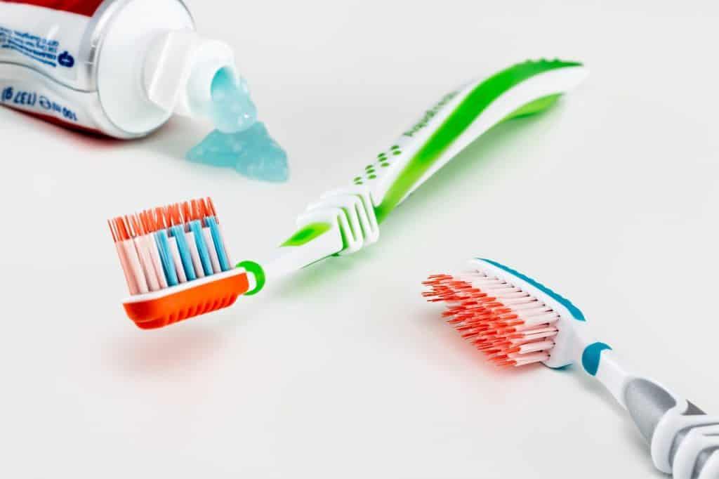 Imagem de duas escovas de dentes sobre superfície branca e uma pasta de dentes aberta do lado.