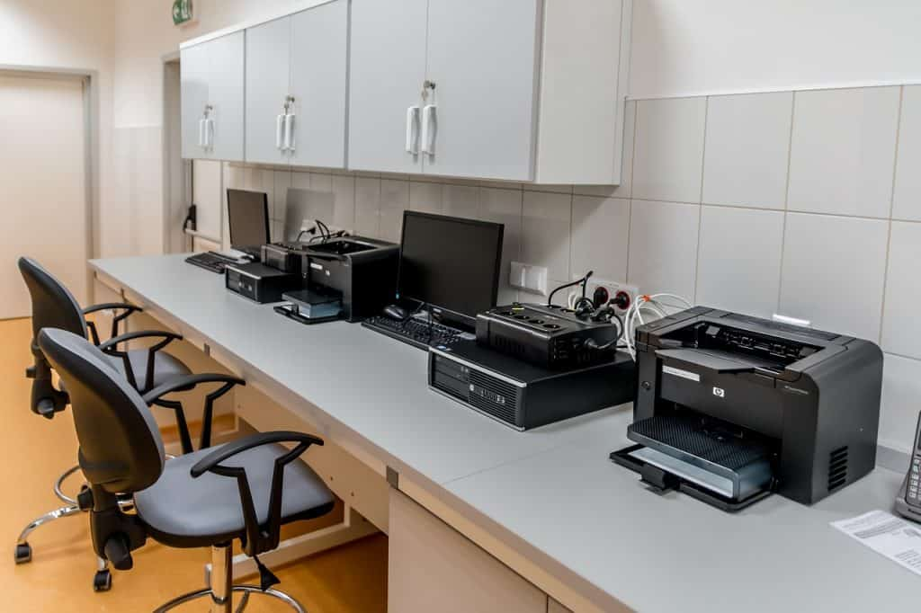 Escritório com mesas brancas uma ao lado da outra. Há duas cadeiras encaixadas nelas. Em cima, podemos ver computadores e impressoras.