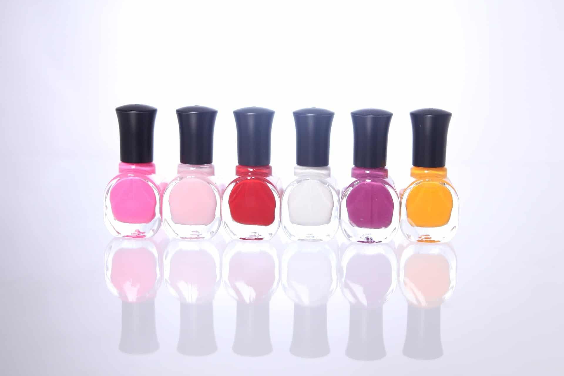 Foto de seis vidros de esmalte de diferentes cores, um ao lado do outro, em um fundo branco.