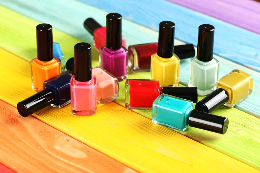 Foto de vários frascos de esmaltes sobre mesa.