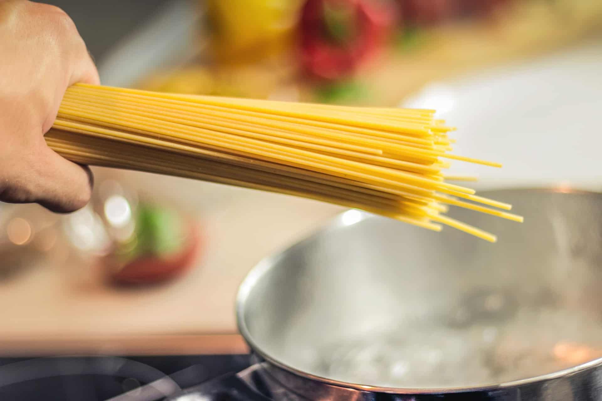 Foto de uma mão segurando uma porção de espaguete, com uma panela de inox ao fundo. Dentro da panela, tem água borbulhando.