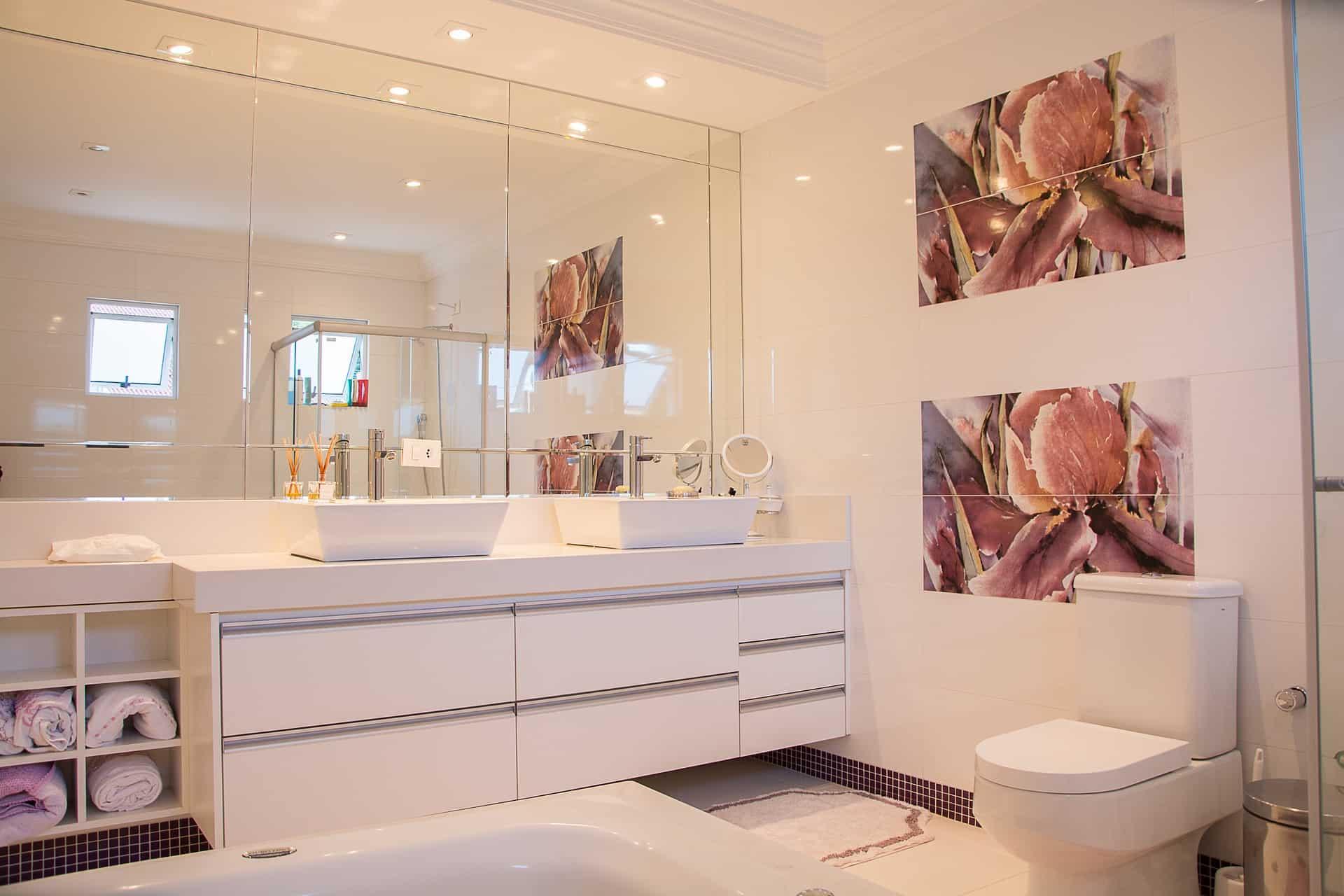 Banheiro espaçoso com móveis brancos e um espelho grande atrás de duas pias.