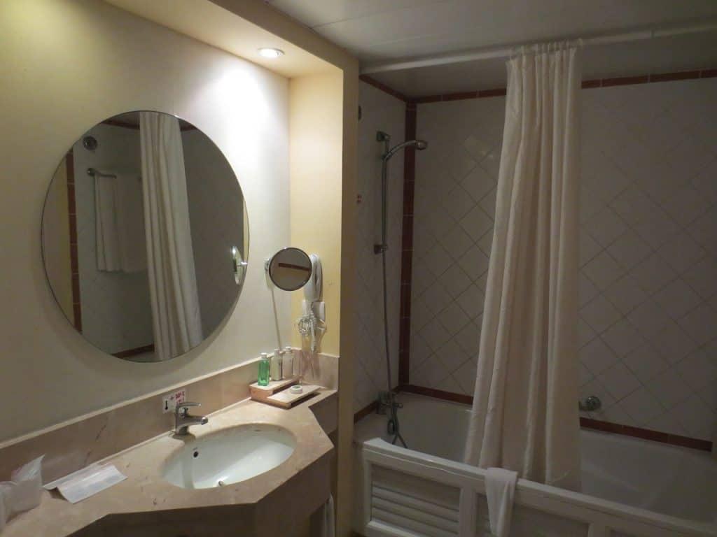 Imagem mostra banheiro com espelho grande redondo e menor ao lado, iluminados.