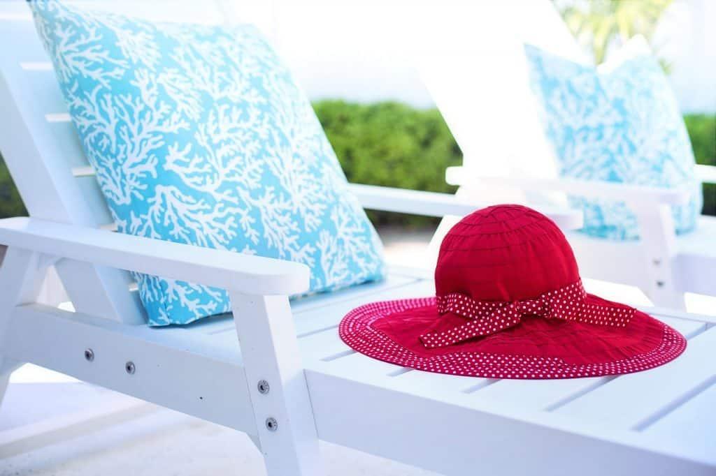 Imagem de espreguiçadeira branca com almofada azul e chapéu vermelho, posicionada em área externa.