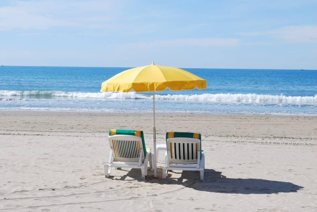 Imagem de duas espreguiçadeiras embaixo de guarda-sol na praia.
