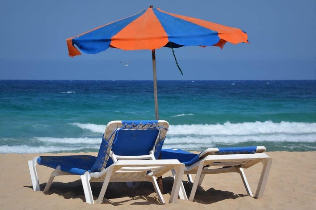 Imagem de duas espreguiçadeiras de plástico na beira da praia.