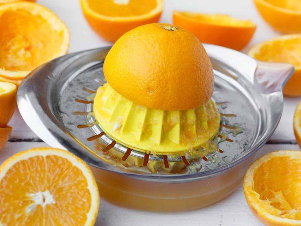Espremedor de laranja manual e pequeno, em aço inox, com laranja sendo espremida e vários pedaços cortados de laranja ao redor.