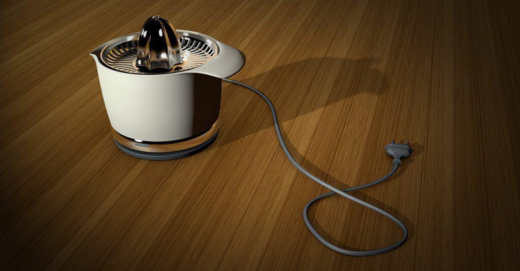 Espremedor de laranja elétrico com base branca e peneira de aço inox, sobre mesa de madeira.