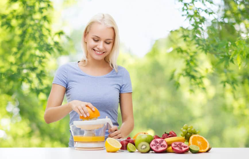 Imagem de mulher espremendo laranja manualmente.