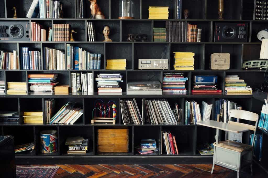 Estante preta grande com diversos nichos. Em alguns, há apenas livros. Em outros, há objetos decorativos, como brinquedos, caixas e outros.