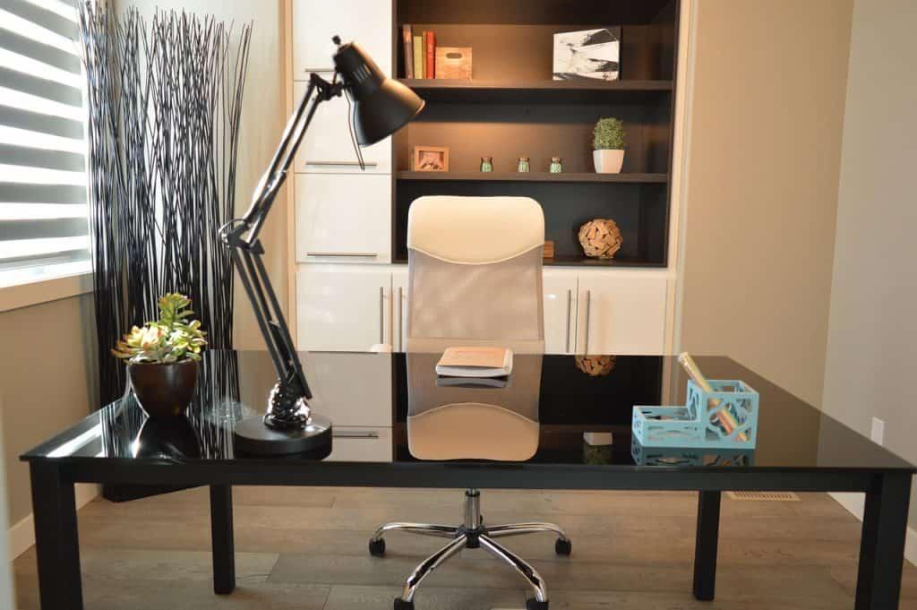 Escritório com uma escrivaninha, cadeira e, acima, uma estante fixa preta de dois nichos.
