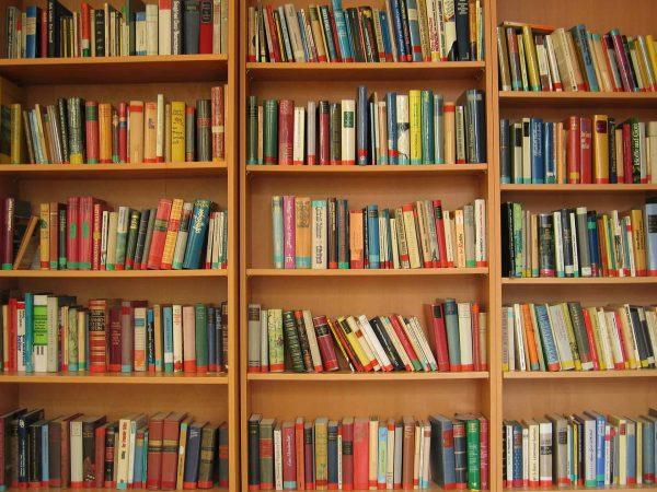 Três estantes, uma do lado da outra, bem iluminadas e cheias de livros de diversos tamanhos e cores.