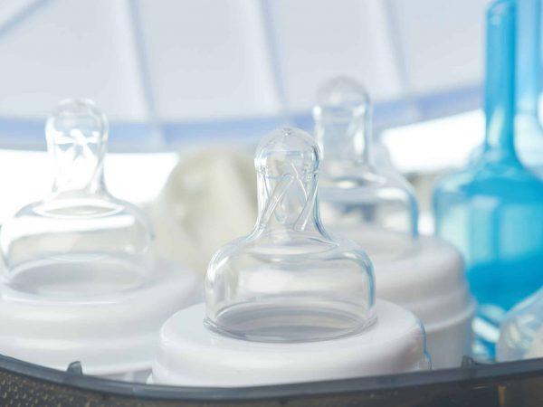Na foto três mamadeiras brancas em um esterilizador de mamadeiras.