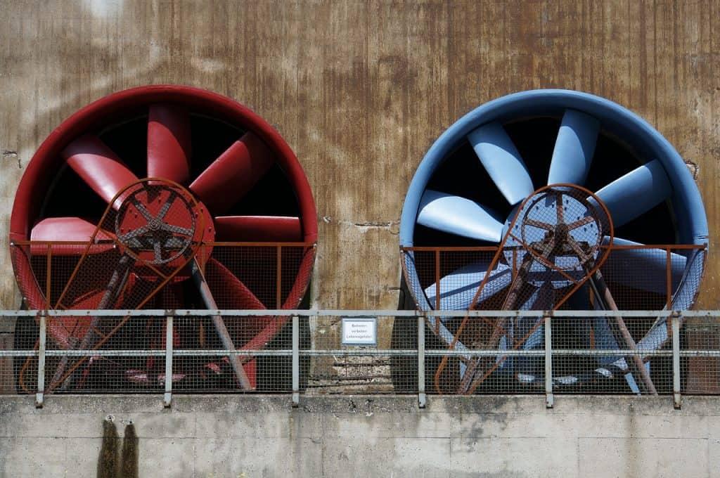 Imagem mostra um exaustor industrial vermelho e um exaustor industrial azul.