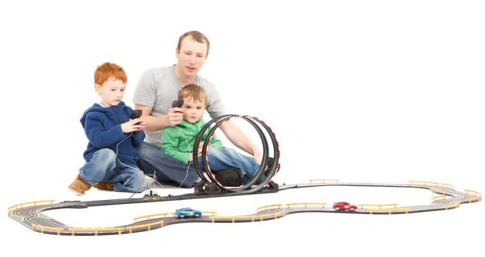 Pai com dois filhos brincando com autorama.