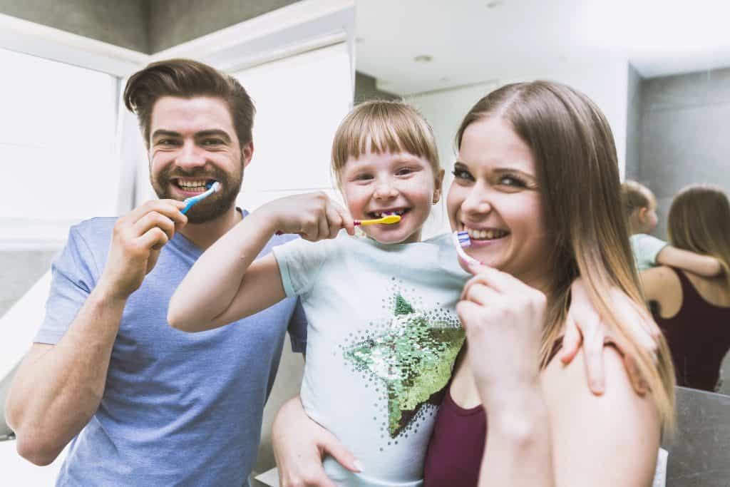 Imagem mostra pai, mãe e filha escovando os dentes durante rotina de cuidados bucais.
