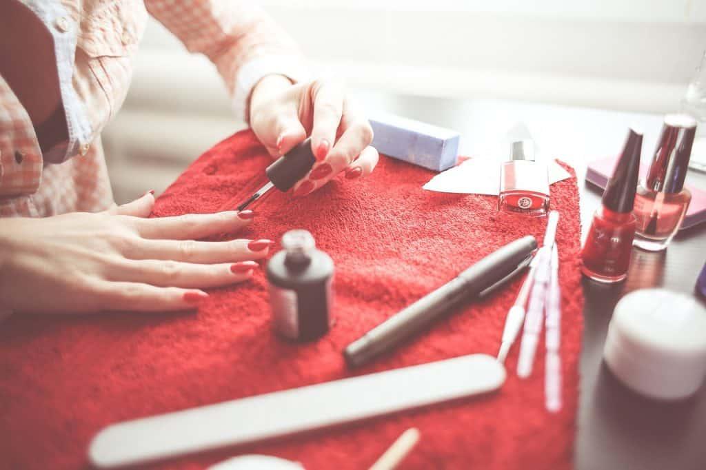 Mulher fazendo unha com itens de manicure.