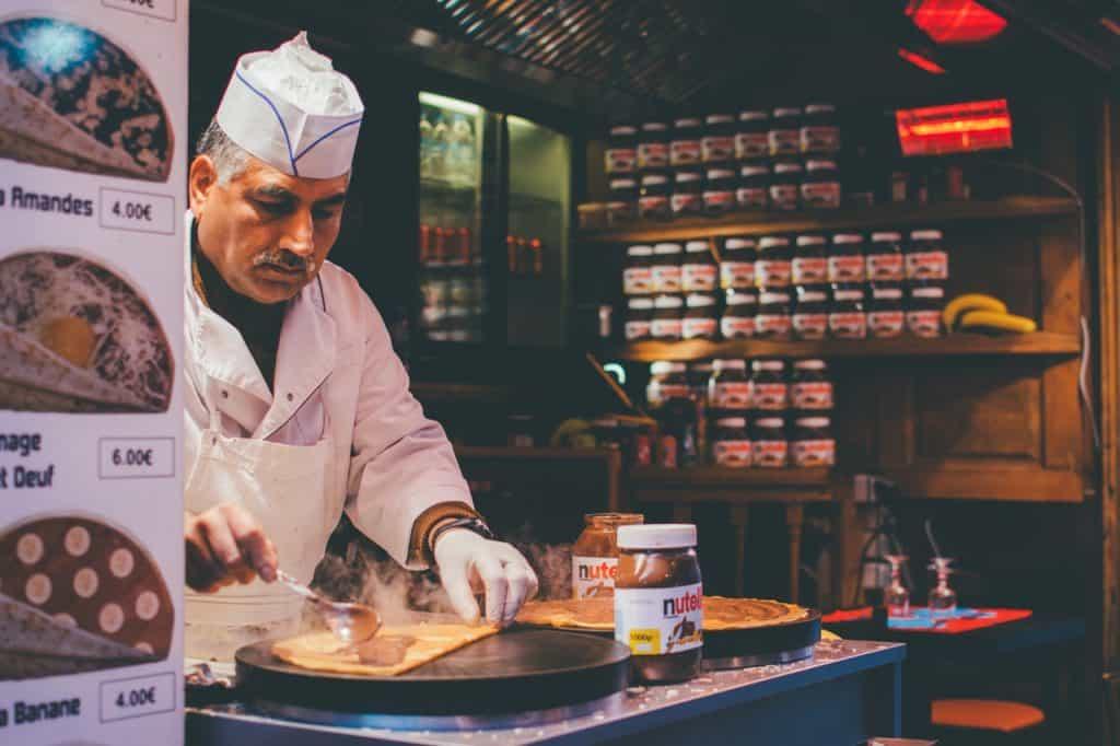 Imagem de um homem preparando um crepe em estilo suíço.