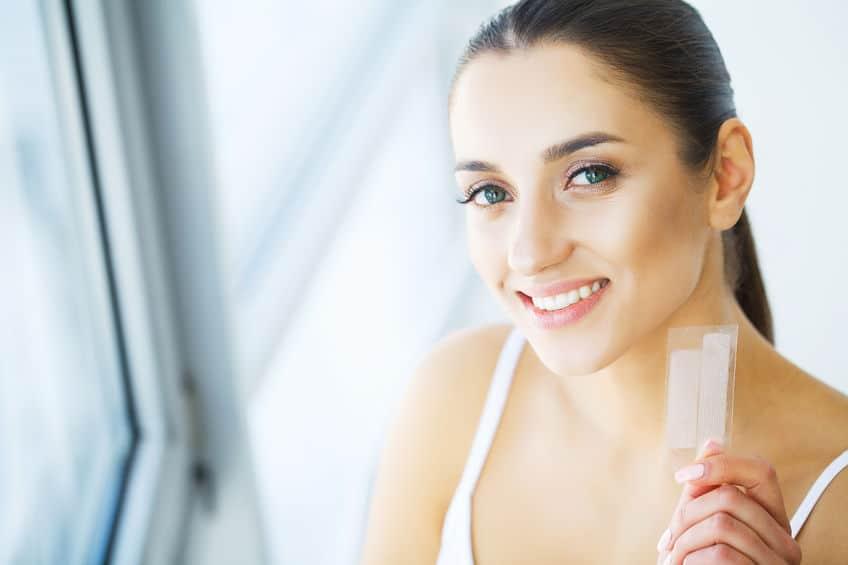 Mulher com dentes brancos segurando clareador dental em forma de fita.
