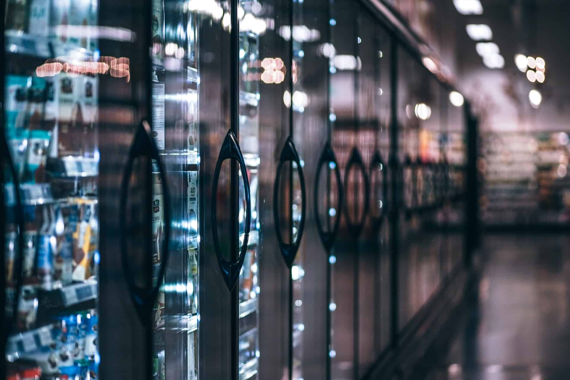 Imagem de uma sequência de freezers verticais, em local que se assemelha com um supermercado, com vários produtos dentro.
