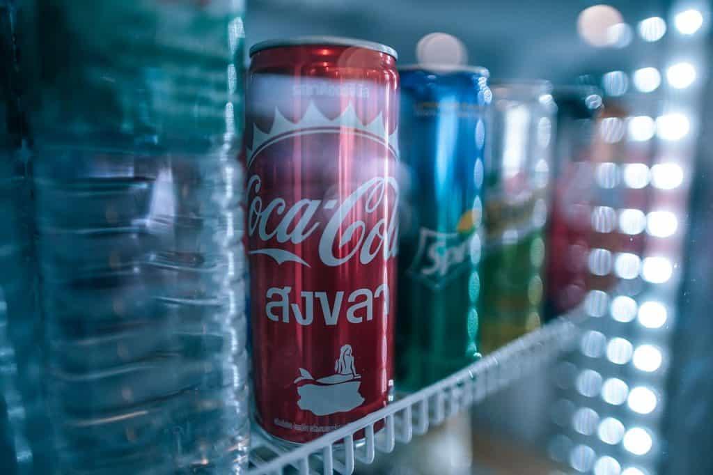 Imagem de uma geladeira com porta de vidro, no interior há garrafas de água e latas de refrigerante.