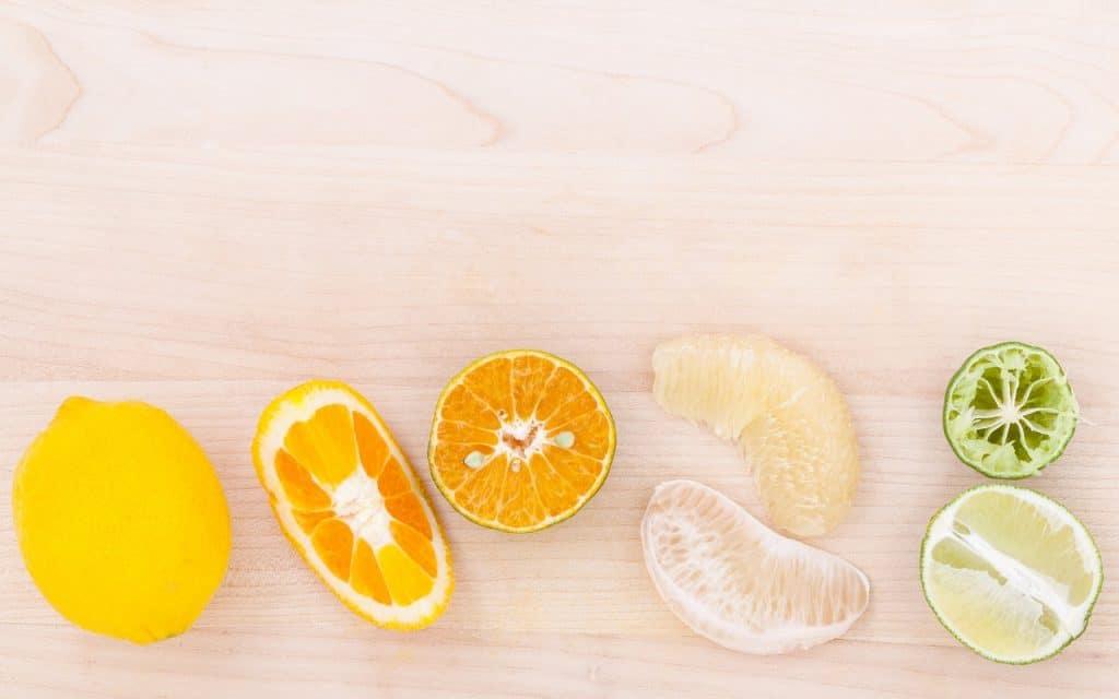 Frutas cítricas em fileira: limão siciliano, pedaço cortado de laranja, gomos de mexerica e metade de um limão.