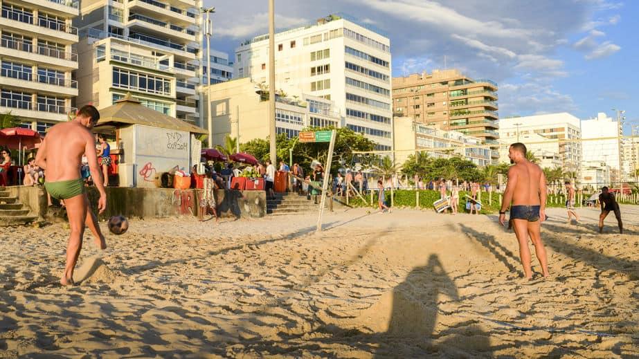 Imagem mostra homens jogando futevôlei na praia de Ipanema no Rio de Janeiro.