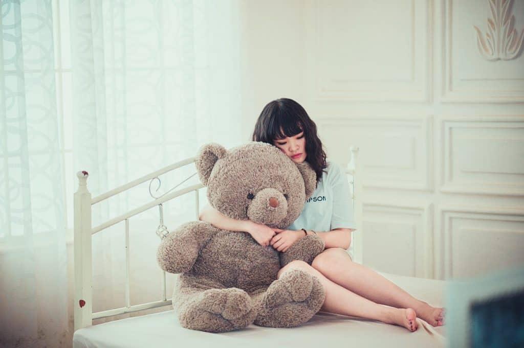 Mulher abraçando urso de pelúcia gigante.