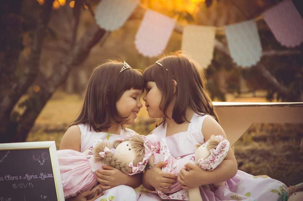 Imagem de irmãs gêmeas brincando com suas bonecas.