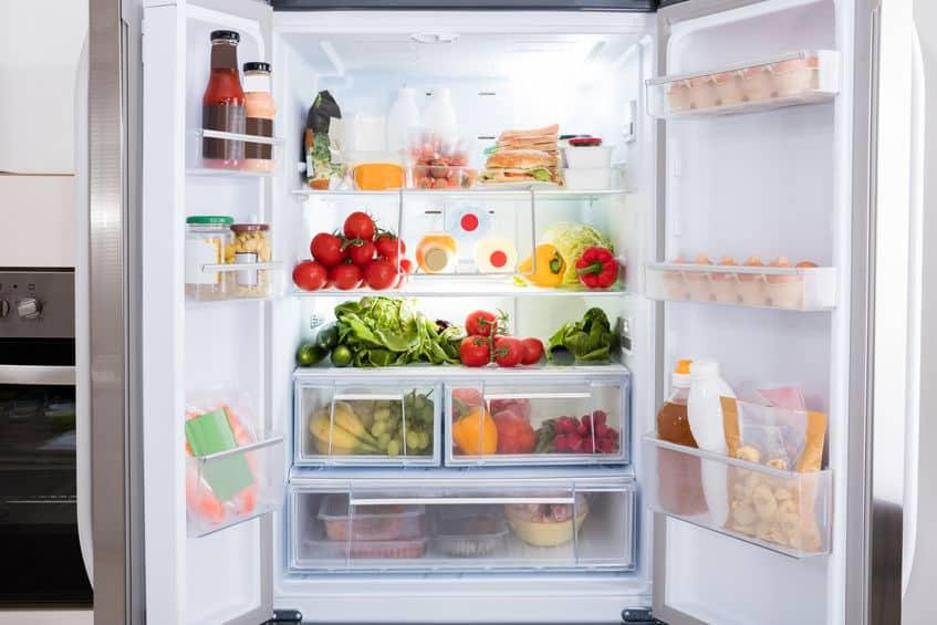 Imagem de geladeira aberta com diversos itens dentro.