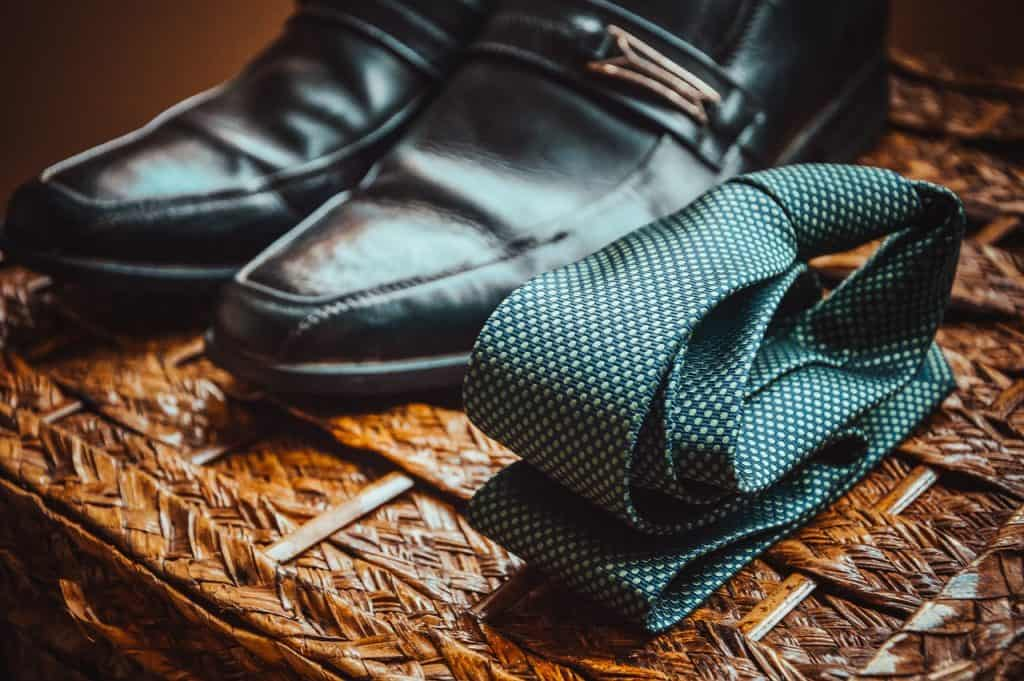 Gravata verde dobrada ao lado de sapato.