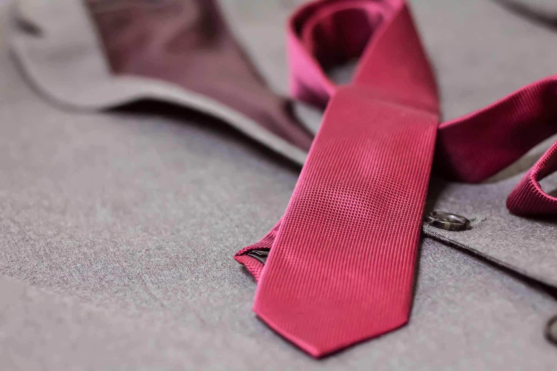 Gravata rosa sobre o terno cinza.