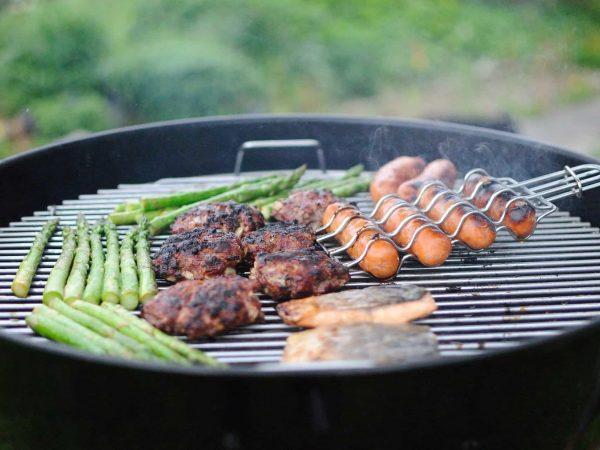 Na foto é possível ver legumes e carnes assando em uma churrasqueira redonda.