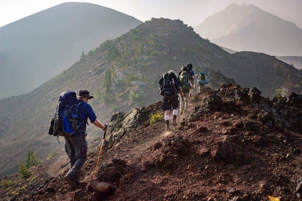 Imagem mostra um grupo de pessoas, em fila, fazendo uma caminhada em uma montanha rochosa. Todas estão com bastões de caminhada.