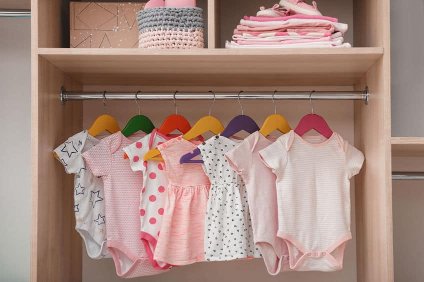 Closet with baby clothes hanging on hangers.