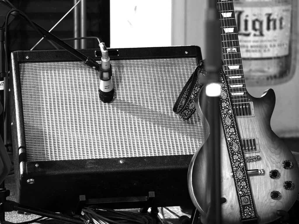 Black and white image of a guitar, placed next to the amplifier that will be used along with it.