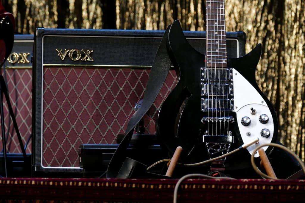 Uma guitarra e dois amplificadores em cima de um palco.