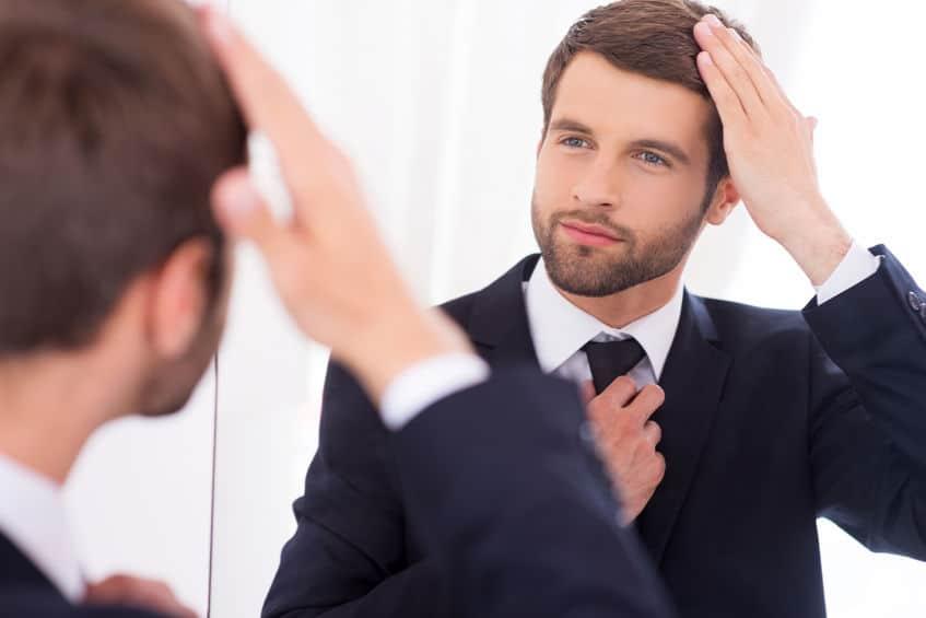 Homem arrumando a gravata e o cabelo na frente do espelho.