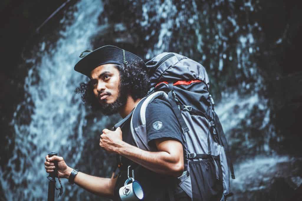 Imagem mostra um rapaz, paramentado com os artigos de aventura, se apoiando num bastão de caminhada, em que segura com a mão direita. Ao fundo, uma queda d'água.