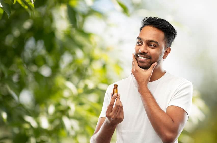 Imagem mostra um homem sorrindo e passando óleo para barba.