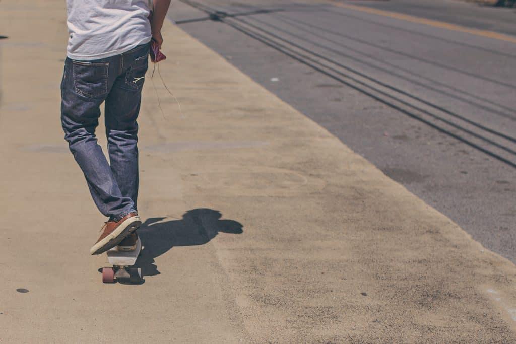 Imagem mostra um rapaz remando seu cruiser pela calçada.