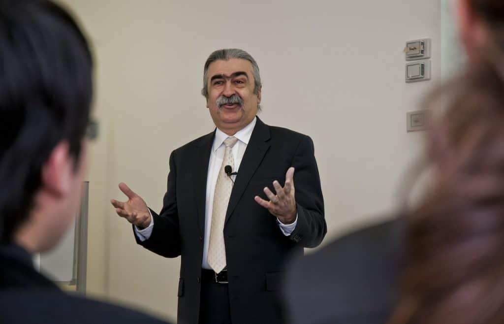 Na foto um homem de terno falando com uma plateia usando um microfone de lapela.