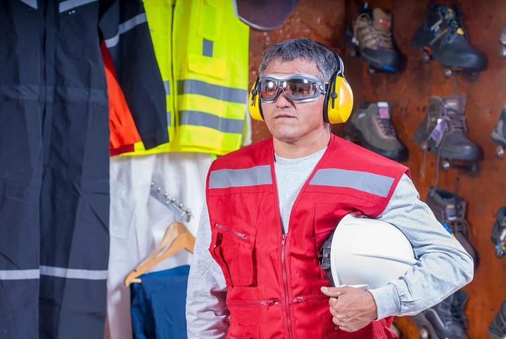 Um homem de cabelos grisalhos usando óculos de proteção e segurando um capacete com a mão direita.