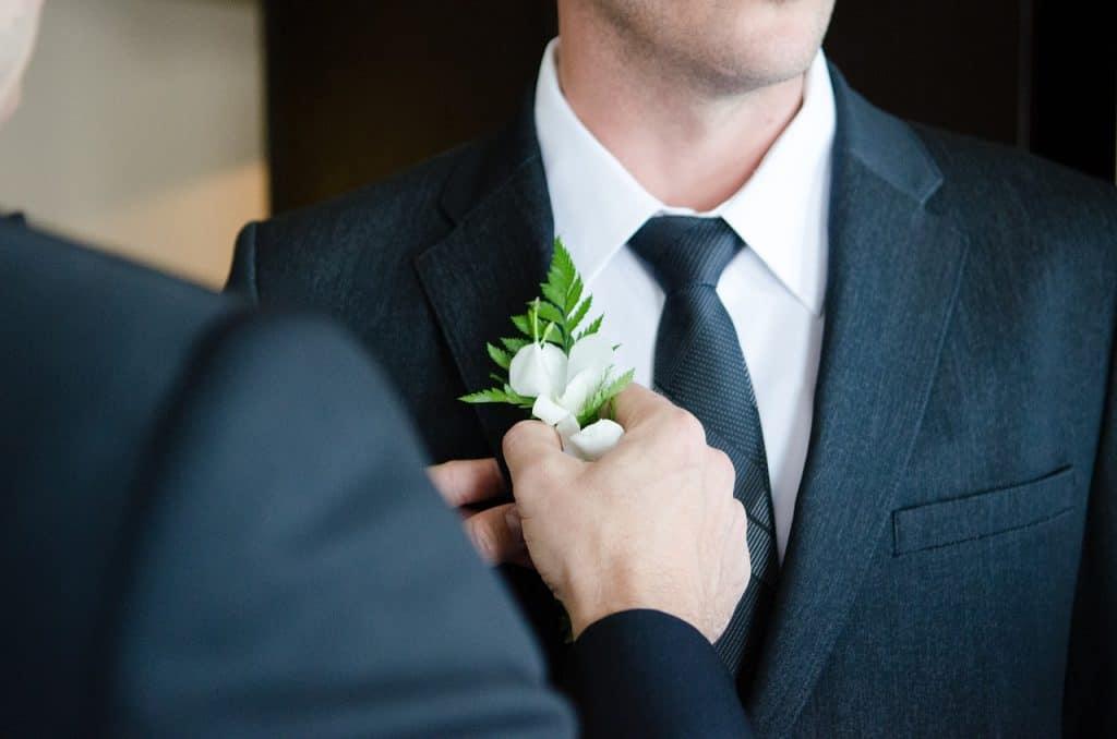 Homens arrumando a gravata em casamento.