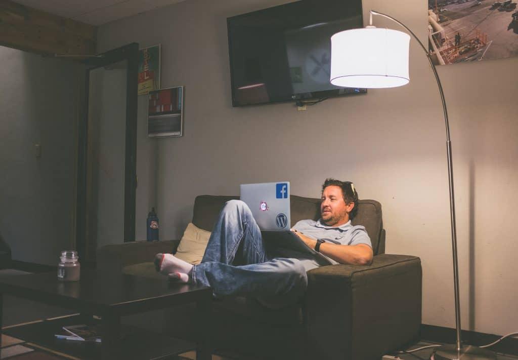 Homem no sofá com notebook e luminária de chão.