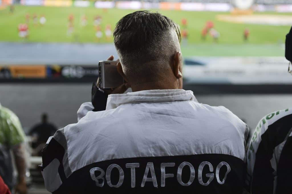 Man from the back using portable radio in football stadium